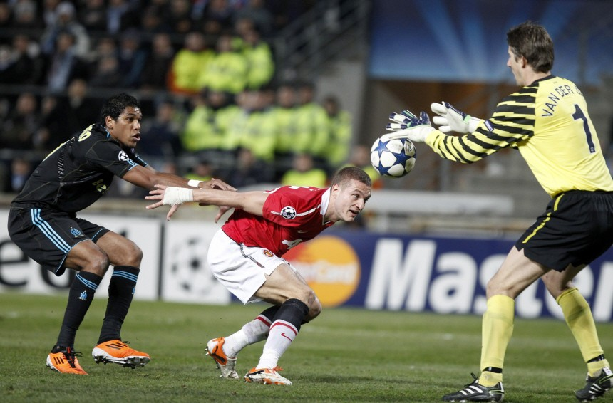 Manchester United's goalkeeper Van der Sar catches the ball with the help of  team mate Vidic against  Olympique Marseille's  Brandao during their Champions League soccer match at the Velodrome stadium in Marseille