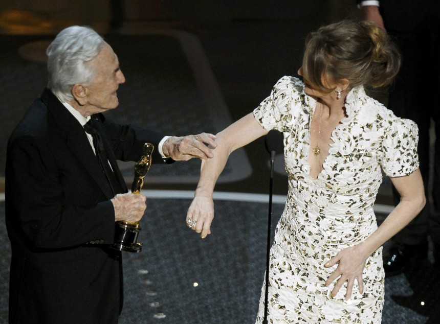 Presenter Kirk Douglas pinches the arm of Melissa Leo before handing her the Oscar for best supporting actress during the 83rd Academy Awards in Hollywood