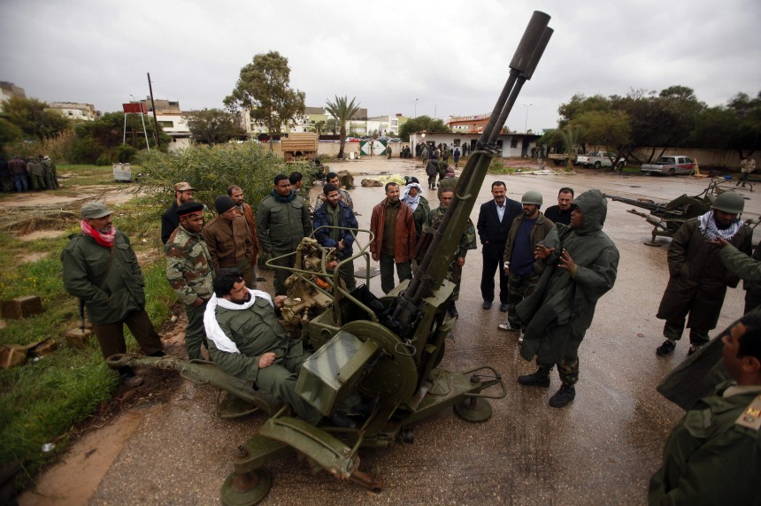 A rebel army officer teaches the use of an anti-aircraft gun to civilians who have volunteered to join the rebel army in Benghazi