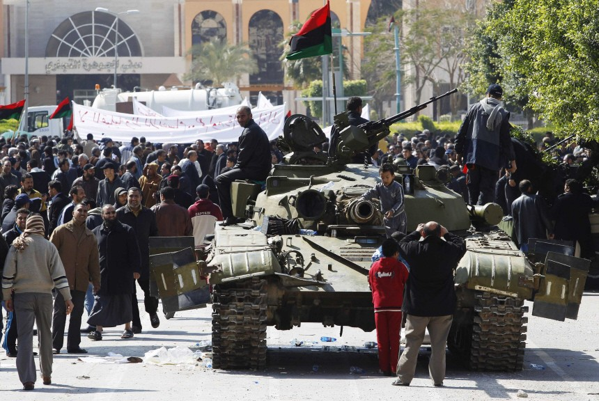 A Libyan army tank manned by soldiers opposed to leader Muammar Gaddafi is surrounded by protesters in the city of Zawiya