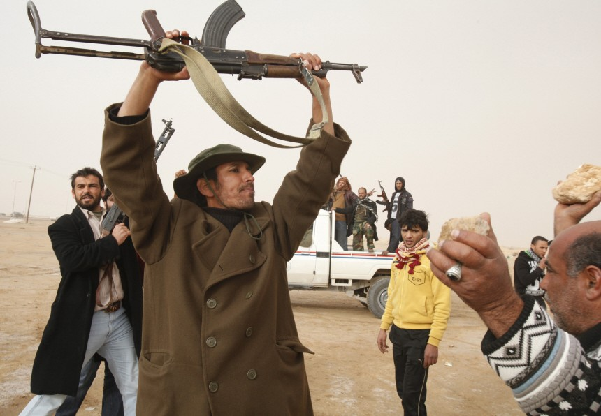 Anti-government tribal rebels shout slogans as they prepare for possible attacks by pro-Gaddafi loyalists at a checkpoint in Ajdabiya area