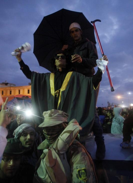 A man dressed as Libyan leader Muammar Gaddafi takes part in a protest against Gaddafi in Benghazi