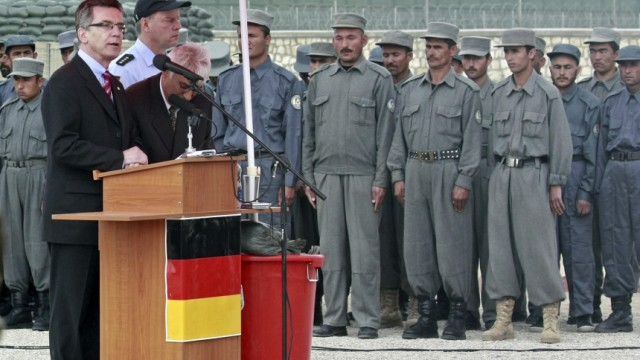 German Interior Minister Thomas de Maiziere addresses Afghan policemen during the opening ceremony of the police training center at the German armed forces Bundeswehr army base in Kunduz