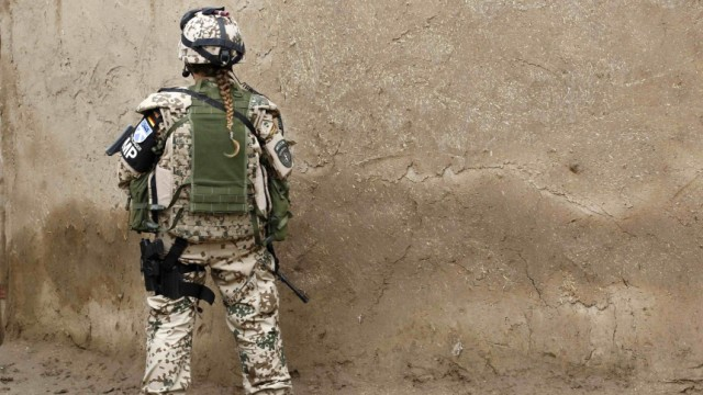 A female German Bundeswehr army soldier with the military police unit Kunduz monitors the area during a mission in a small village in the outskirts of Kunduz