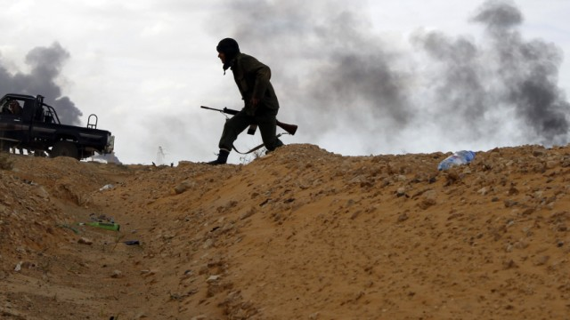 A rebel fighter runs for cover near a burning gas storage terminal during a battle on the road between Ras Lanuf and Bin Jawad