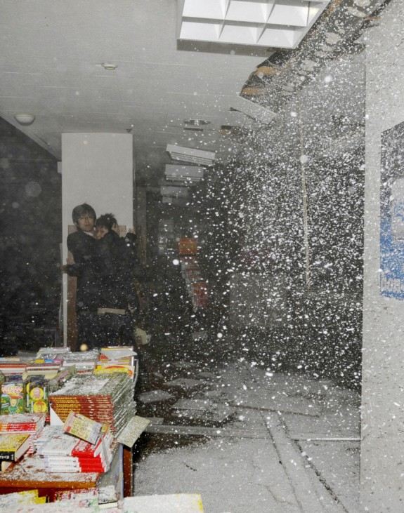 People take shelter as a ceiling collapses in a bookstore during an earthquake in Sendai