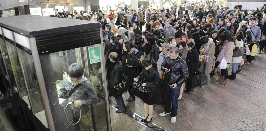 People line up in front of public telephone booths at Shibuya station  in Tokyo