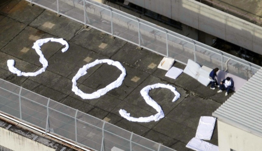 People wait to be rescued atop a building with the letters 'SOS' after an earthquake in Kesennuma
