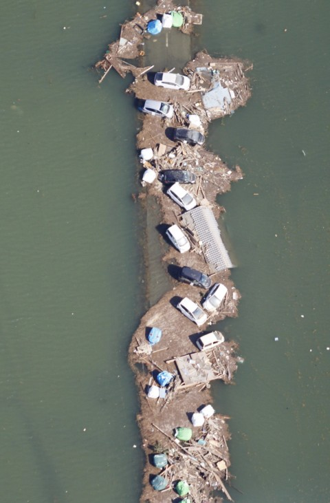 Vehicles are seen with the rubble in flood waters near the coastal town of Sendai after the earthquake and tsunami that devasted the region