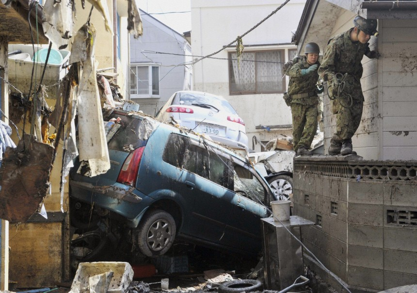 Japan Self-Defence Force troops walk atop a wall to get around a car tossed by a tsunami and earthquake in northeastern Japan