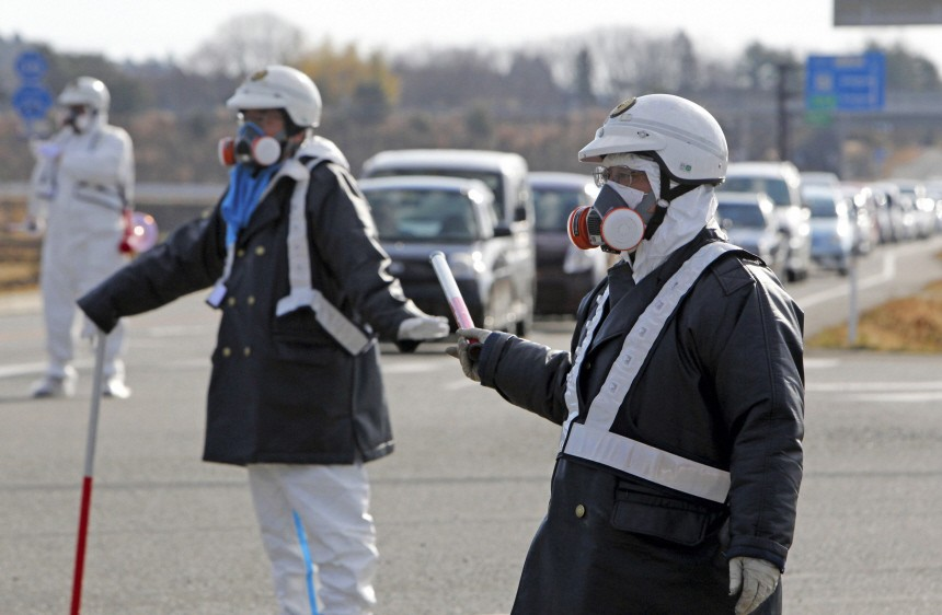 Police officers wearing respirators guide people to evacuate away from the Fukushima Daiichi 1 nuclear plant in Tomioka Town