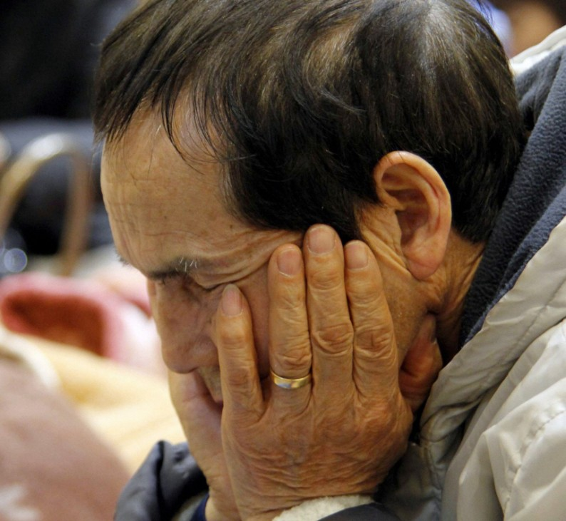 A man sits in an evacuation centre for people evacuating from the area around the Fukushima Daiichi Nuclear Plant