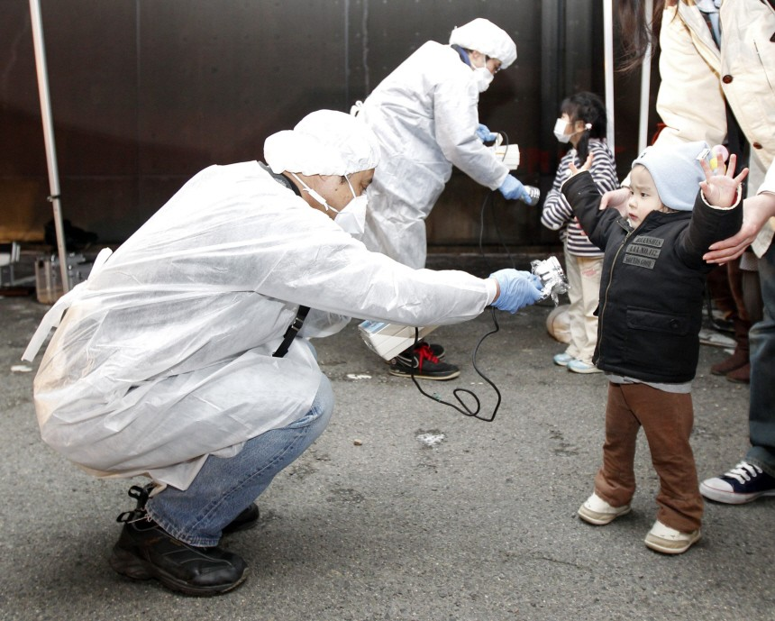 Officials in protective gear check for signs of radiation on children who are from the evacuation area near the Fukushima Daini nuclear plant in Koriyama