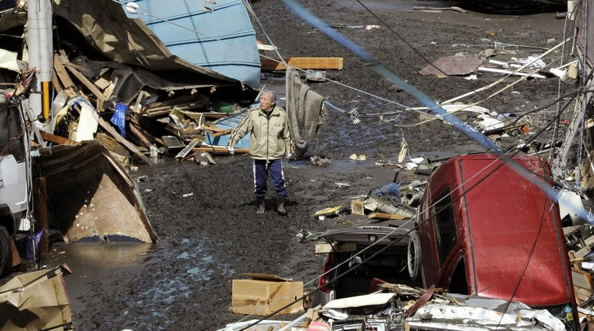A man walks among debris and strewn boats after a tsunami in Miyako City, Iwate Prefecture