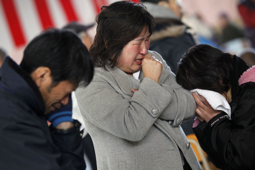 Survivors cry at a shelter in a village ruined by an earthquake and tsunami in Rikuzentakata in Iwate prefecture, northeast Japan