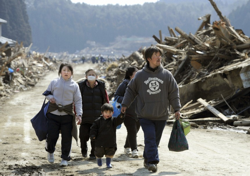 A family walks past buildings destroyed by a tsunami in Minamisanriku, Miyagi Prefecture, in northern Japan after the magnitude 8.9 earthquake struck the area