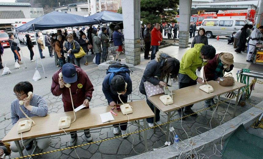 People use temporary installed telephones after an earthquake and tsunami struck Ofunato City, Iwate Prefecture in northern Japan