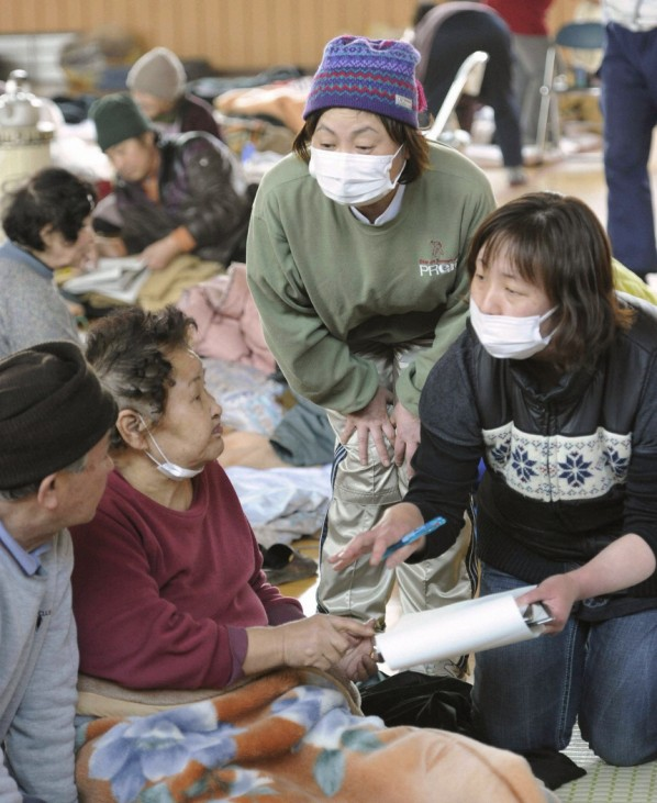 A nurse talks to evacuees at an evacuation centre after a magnitude 8.9 earthquake and tsunami hit Otsuchi Town, Iwate Prefecture