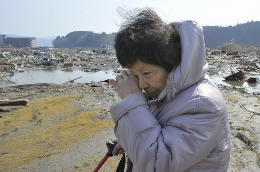 A woman searches for her missing husband amid debris in Minamisanriku, Miyagi Prefecture in northern Japan