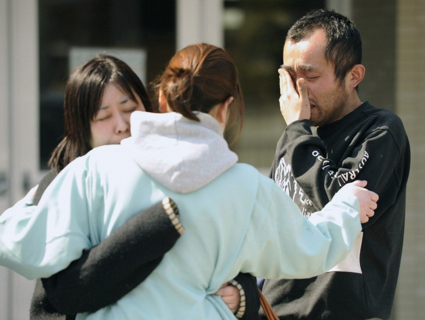 A man cries outside an evacuation center after learning that a friend perished after an earthquake and tsunami struck Higashimatsushima City