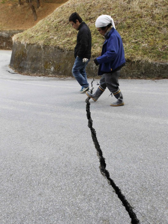 A man steps over a crack in the road as he walks towards the devastated area of Rikuzentakata, northern Japan after the magnitude 8.9 earthquake and tsunami struck the area