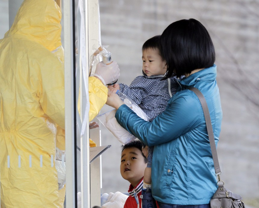 A technician in protective gear scans a child for signs of radiation at a makeshift facility to screen, cleanse and isolate people with high radiation levels in Nihonmatsu