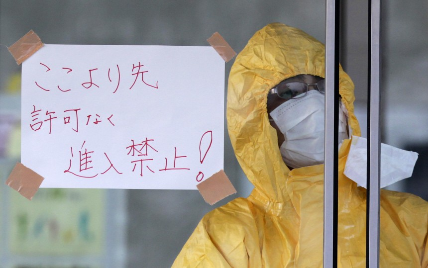 A technician in protective gear looks out of a window at a makeshift facility to screen, cleanse and isolate people with high radiation levels in Nihonmatsu, northern Japan