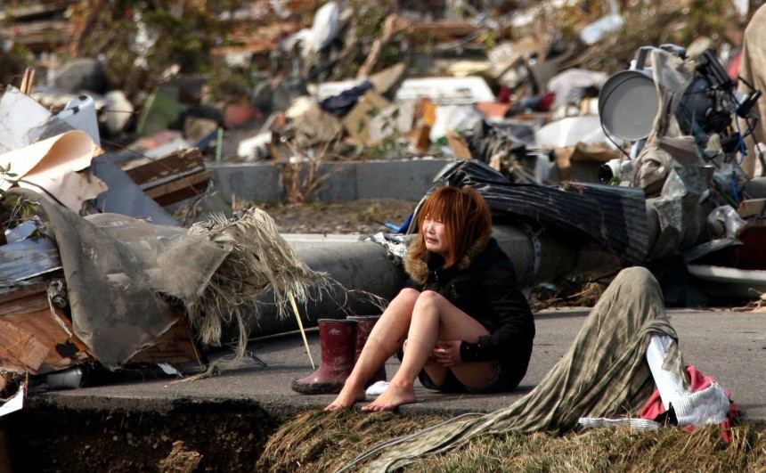 A woman cries while sitting on a road amid the destroyed city of Natori, Miyagi Prefecture in northern Japan