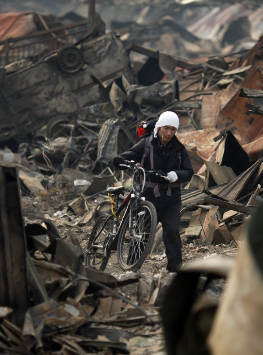 A Japanese man pushes his bicycle through the remains of the devastated town of tsunami-hit Otsuchi