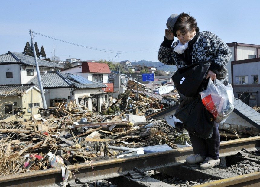 An elderly tsunami survivor walks on the raulway