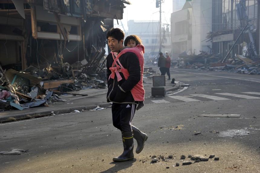 A man walks devasted street in Kesennnuma