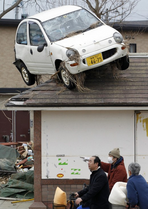 A car is seen on the rooftop of a house near residents talking in an area hit by an earthquake and tsunami in Sendai, northeastern Japan