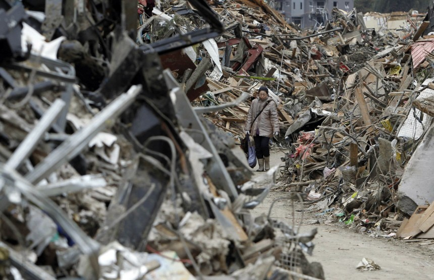 Woman walks amidst debris in an area hit by an earthquake and tsunami in Rikuzentakata