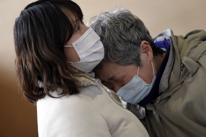 A woman (L) and her maternal aunt cry at a shelter as they reunite for the first time after an earthquake and tsunami in Rikuzentakata in Iwate prefecture, northeast Japan