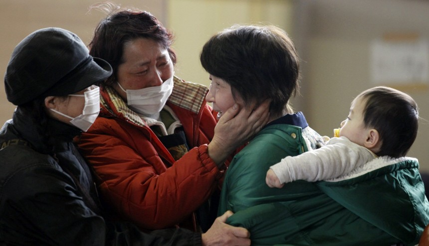 A woman reunites with her relatives at a shelter for the first time after an earthquake and tsunami in Rikuzentakata