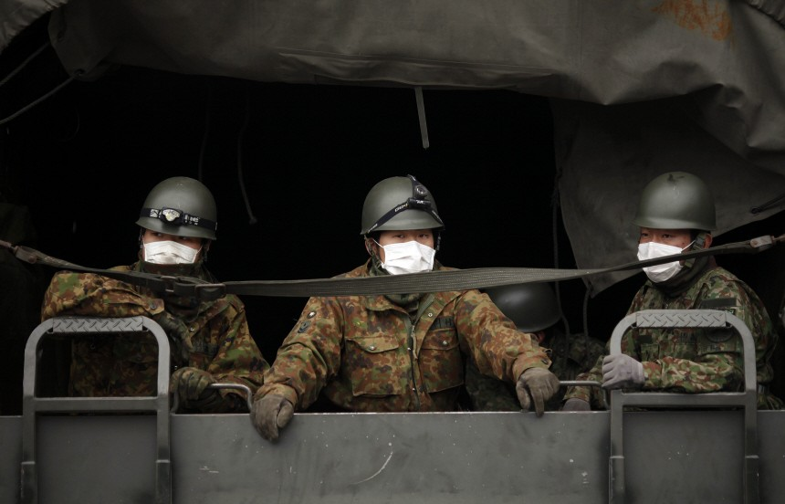 Japan Self-Defense Force officers wearing masks arrive at the devastated residential area of Otsuchi