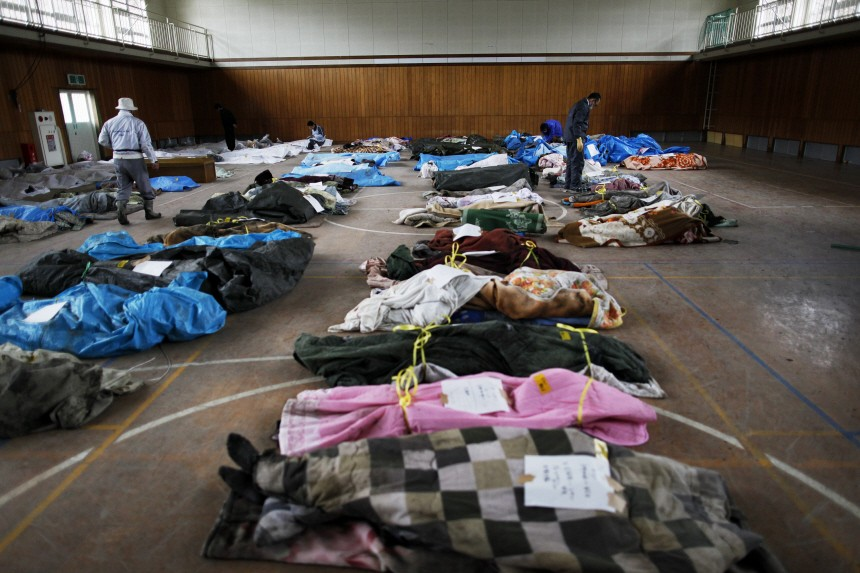 Bodies found in the ruins of the devastated residential area of Otsuchi are collected in a sports hall