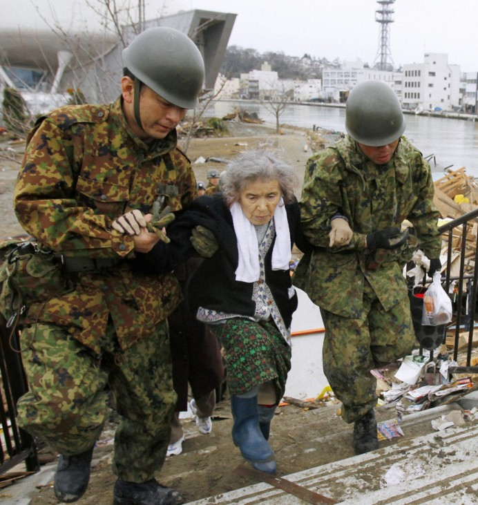 A woman who had been stranded in an isolated evacuation center for five days is rescued by officers of the Japan Self-Defense Forces in Ishimaki Town