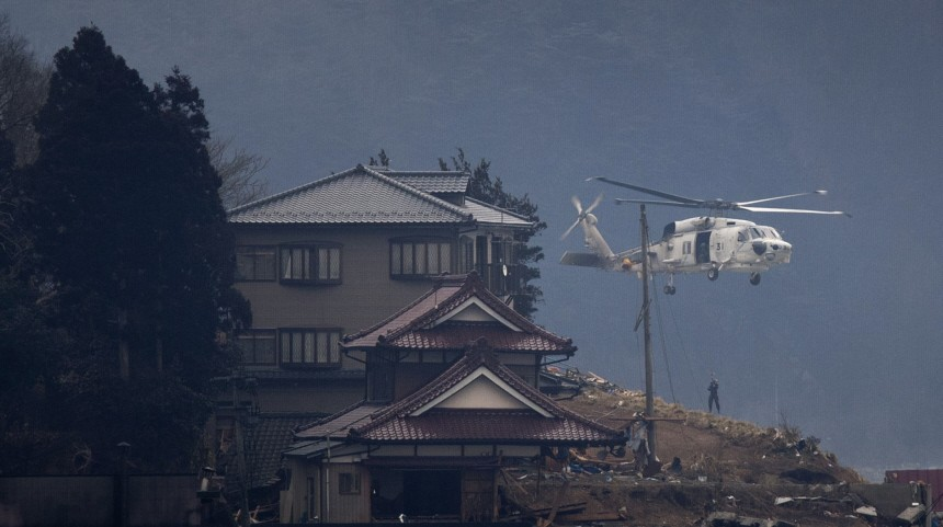 A rescue helicopter lowers a man in search of victims along a remote hillside near Kesennuma City days after the area was devastated by a magnitude 9.0 earthquake and tsunami
