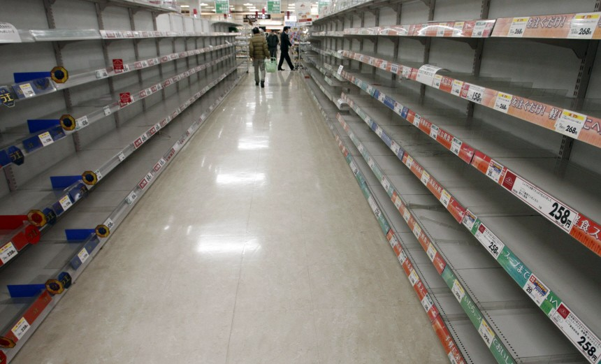 People shop for food from almost empty shelves at a big-box supermarket in Tokyo