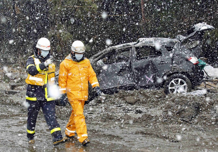 Rescue workers walk past a damaged car during heavy snowfall at a factory area devastated by an earthquake and tsunami in Sendai, northern Japan