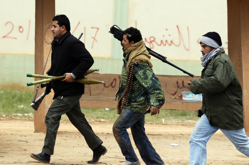 Rebel fighters run for cover as shells fired by fighters loyal to Libyan leader Muammar Gaddafi explode nearby, in Benghazi