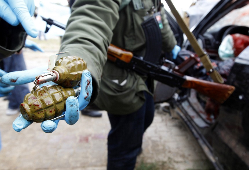 A rebel fighter shows hand grenades found on fighters loyal to Libyan leader Muammar Gaddafi after they were killed by rebel fighters in Benghazi