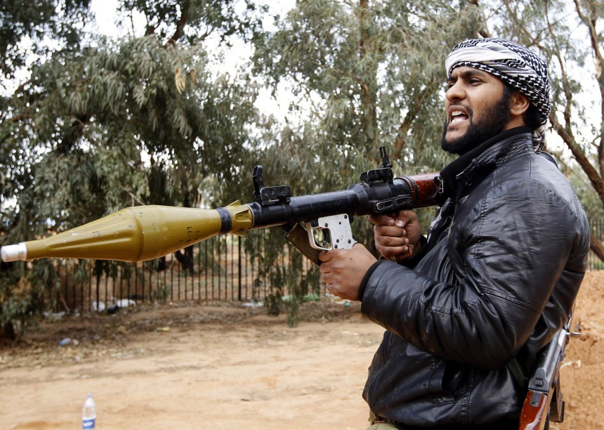 A rebel fighter holds a RPG launcher as he shouts 'Allahu Akbar!' in Benghazi