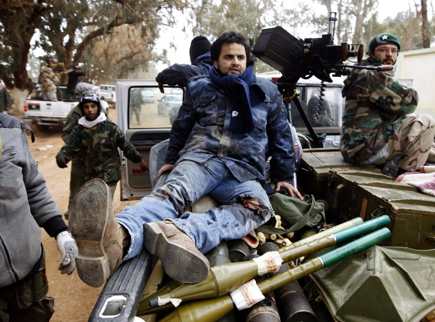 An injured rebel fighter sits in a car in Benghazi