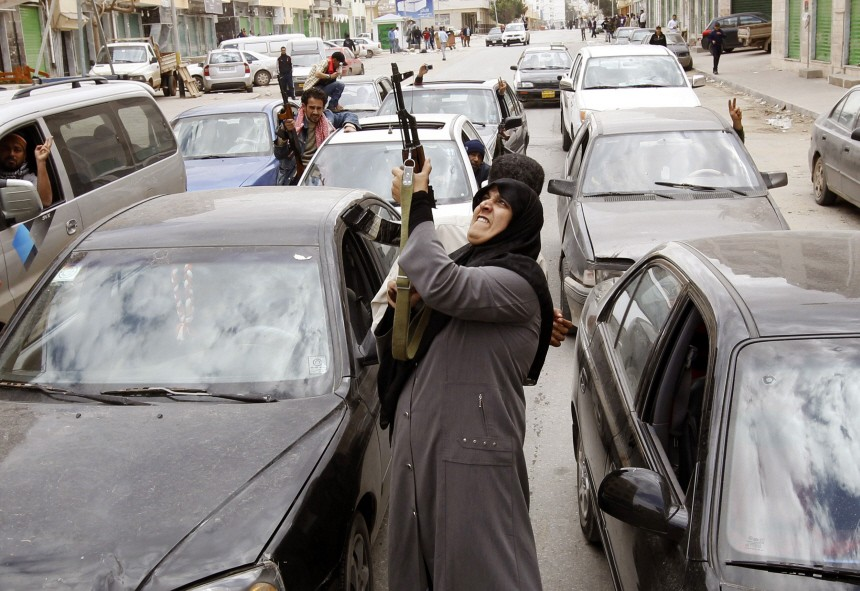 A woman rebel fighter supporter shoots an AK-47 rifle as she reacts to the news of the withdrawal of Libyan leader Muammar Gaddafi's forces from Benghazi