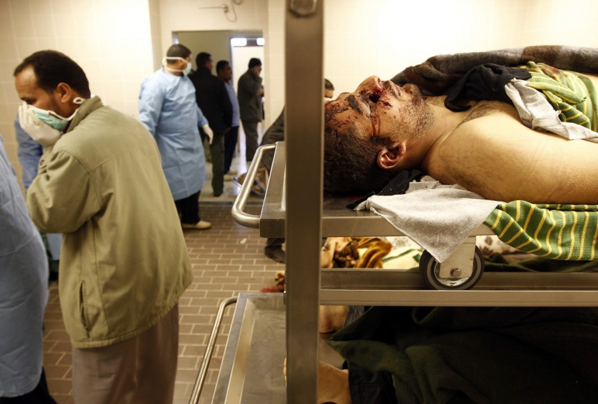 Medical workers look at bodies of rebels killed in recent fighting with troops loyal to Libyan leader Muammar Gaddafi in a morgue of a hospital in Benghazi
