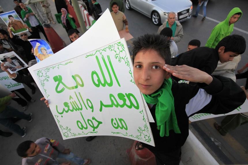 A supporter of Libya's leader Muammar Gaddafi holds a sign outside Bab Al-Aziziyah, Gaddafi's heavily fortified Tripoli compound