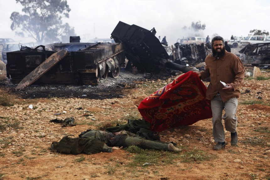 A Libyan man carries a blanket to cover the body of a Muammar Gaddafi loyalist soldier near Benghazi