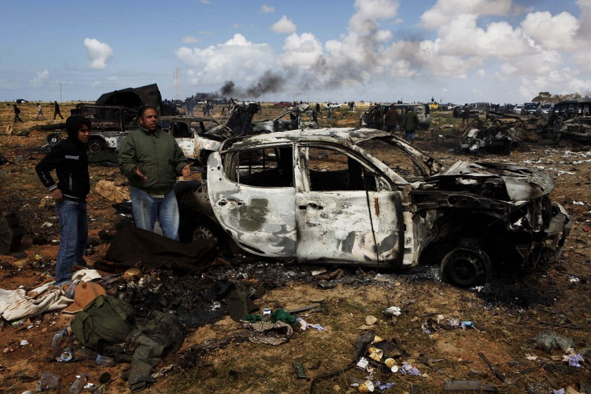 People stand near bodies that are under a blanket, of Muammar Gaddafi loyalist soldiers on the outskirts of Benghazi
